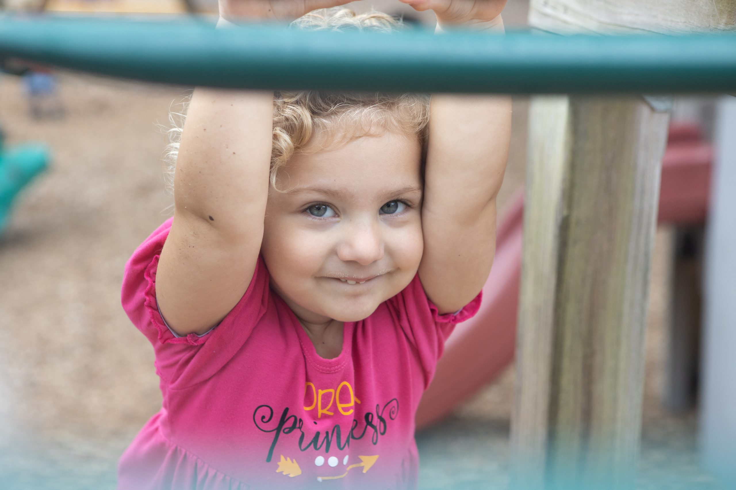 Adorable child looks out from under a rail on the playground