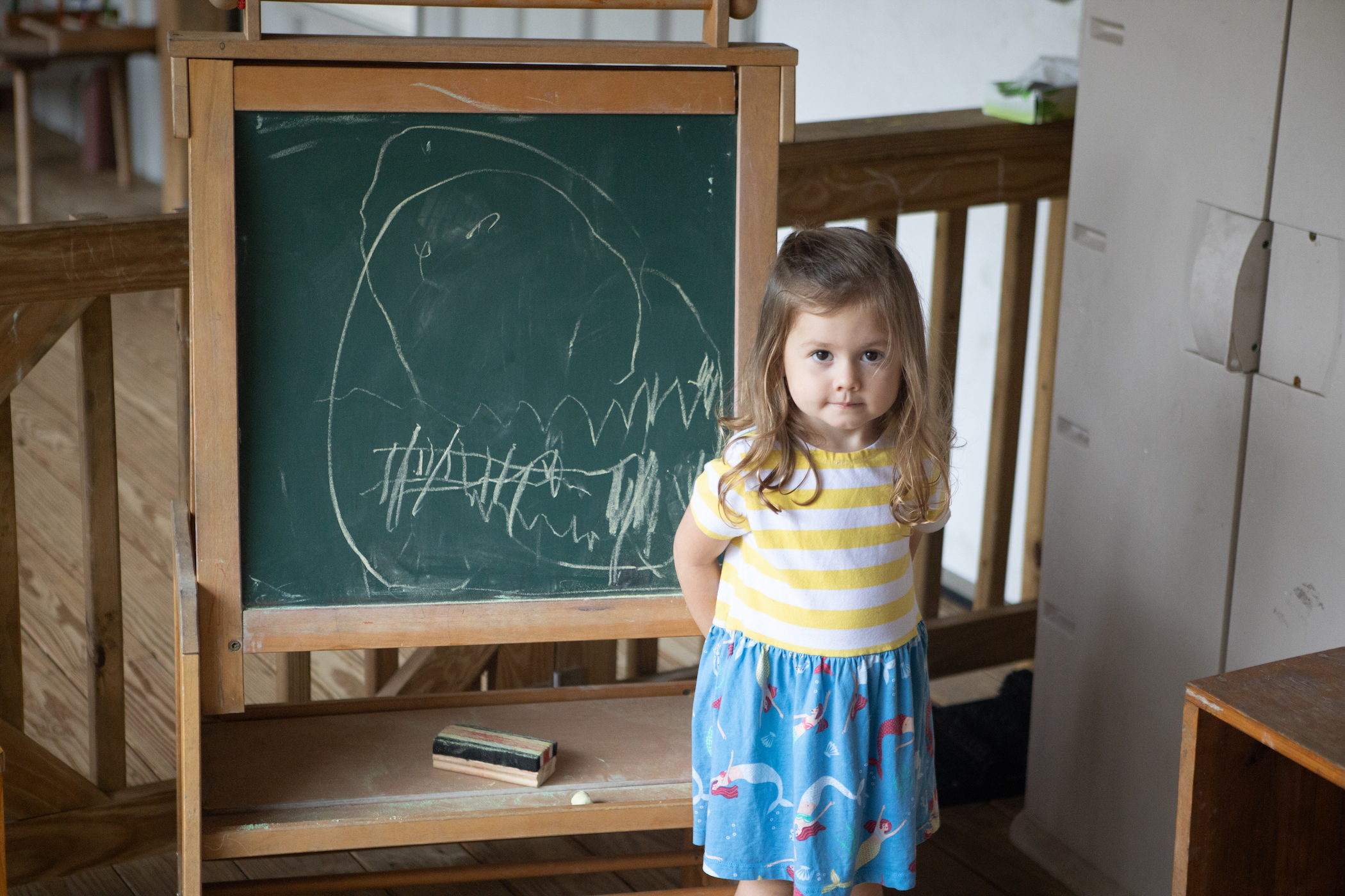 Girl stands by outdoor chalkboard
